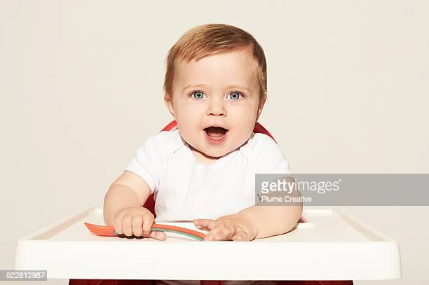 Happy baby holding spoon
