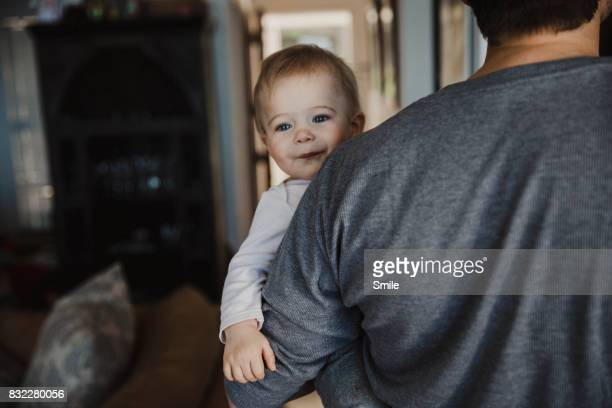Happy baby looking over father's shoulder