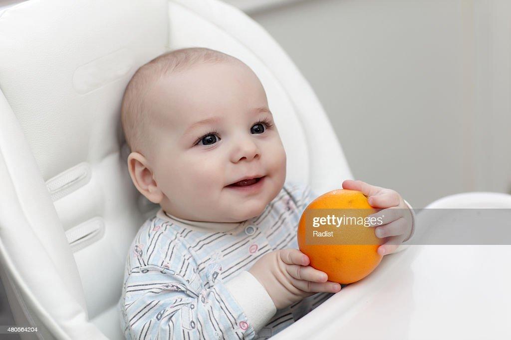 Happy baby with orange : Stock Photo