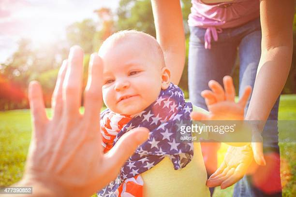 Happy baby wrapped in American flag on the Independence Day