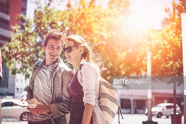 Happy backpackers traveling in city