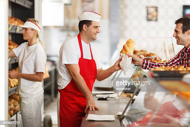 Happy baker and his customer in bakery.