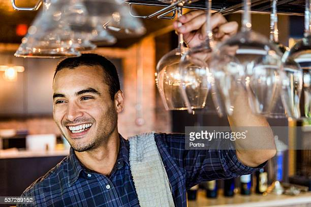 Happy bartender arranging wineglasses