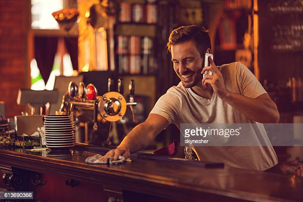 Happy bartender cleaning bar counter and talking over cell phone.