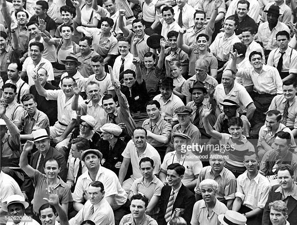 Happy baseball fans in the bleachers at Yankee Stadium New York New York late 1930s