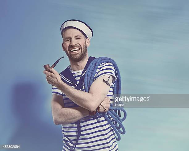Happy bearded sailor man holding pipe and rope