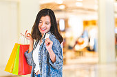 Happy beautiful Asian woman smile at credit card, hold shopping bags, copy space on shopping mall background. Shopaholic people, rich girl spending money lifestyle, or department store payment concept