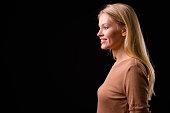 Studio Portrait Of Beautiful Blonde Woman Smiling Against Black Background