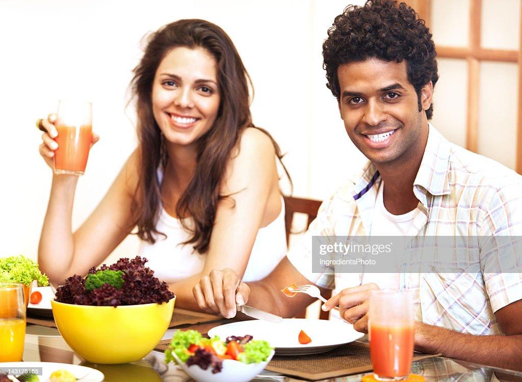 Happy beautiful brazilian couple having lunch at home. : Stock Photo