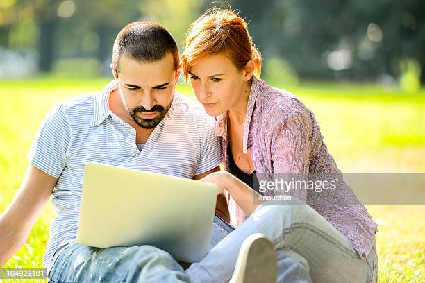 Happy Beautiful couple using Laptop outdoors