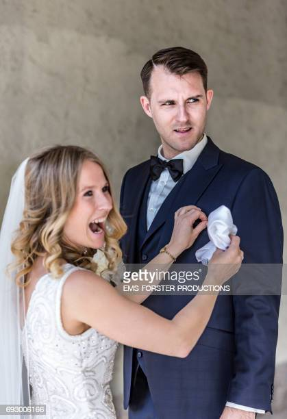 happy beautiful long blonde haired bride with a big toothy smile wearing her white wedding dress and veil attaches a white dress handkerchief to her tall brown haired groom's wedding suit in front of a wall on a sunny day right before the wedding ceremony