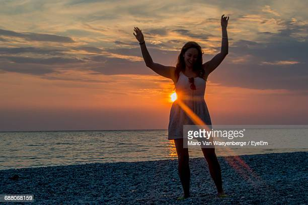 Happy Beautiful Woman Dancing At Beach Against Sky During Sunset
