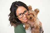 Closeup portrait of smiling young attractive woman looking at camera and embracing Yorkshire terrier. Pet concept. Isolated front view on white background.