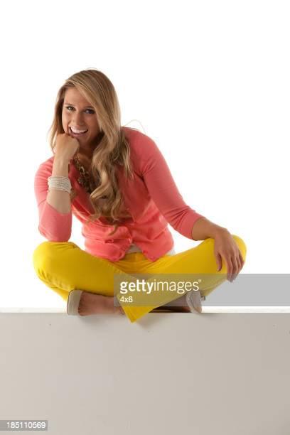Glückliche schöne Frau sitzt auf einer Wand