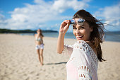 Portrait of happy beautiful woman standing on beach with friend laughing