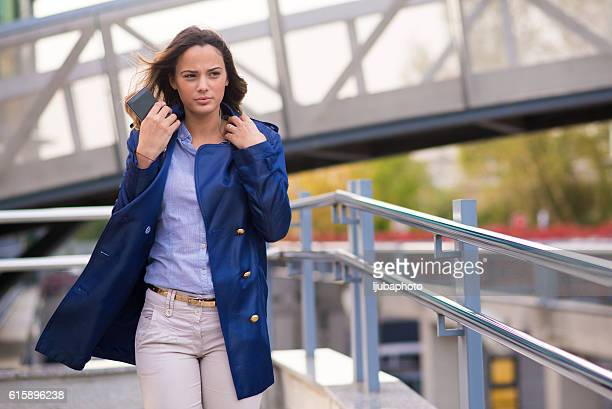 Happy beautiful woman walking  and holding  smart phone