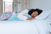 Happy beautiful young black woman lying down in the bed sleeping'n