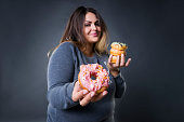 Happy beautiful young caucasian plus size model posing with donuts on a gray studio background, fast food and unhealthy nutrition concept