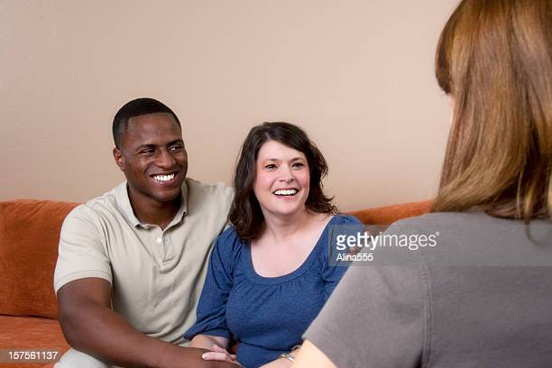Happy bi-racial couple on the couch talking to a consultant