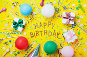 Happy birthday background or greeting flyer from gifts or presents. Colorful holiday supplies on yellow table top view. Flat lay style.