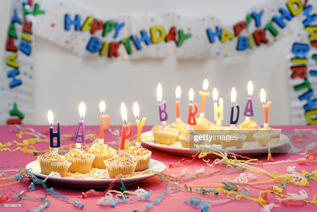 Happy Birthday candles on top of small cakes : Stock Photo