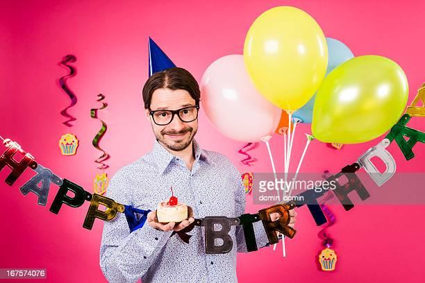 ハッピーバースデーツーユーます。オタク男性、小さなケーキを片手に、風船
