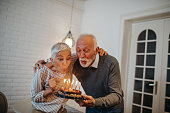Senior couple blowing out candles