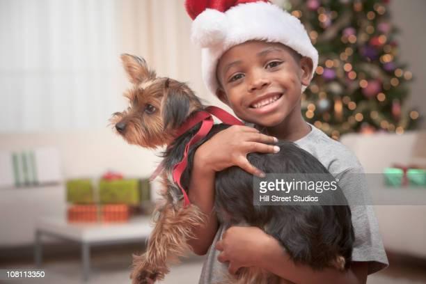 Happy Black boy in Santa hat holding small dog