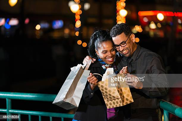 Heureux couple noir un sac-cadeau d'ouverture à l'extérieur de nuit