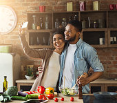 Happy black couple taking selfie with smartphone while preparing healthy salad at kitchen