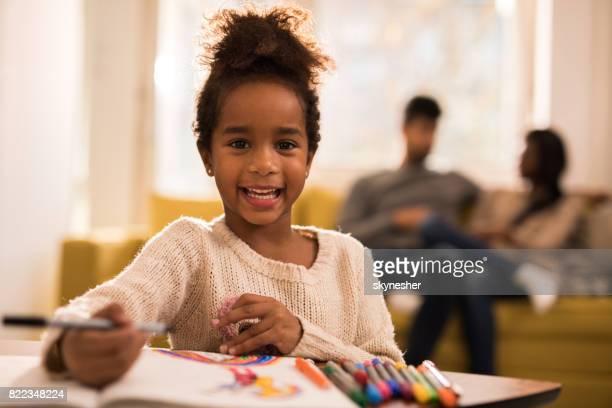 Fille noire heureuse s'amuser en dessinant et en regardant la caméra.