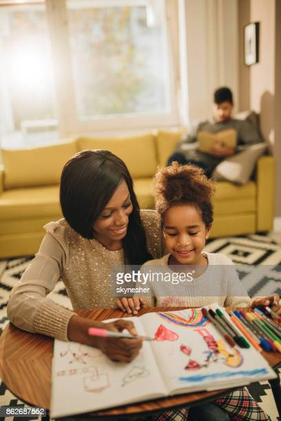 Happy black mother and daughter coloring and having fun in the living room.