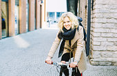 Happy Blond Girl Cycling In The City