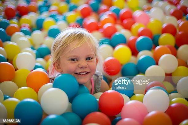 Happy blond girl plays in a ball pool
