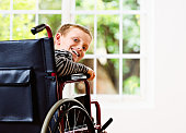 Happy blond schoolboy in wheelchair seems to be recovering