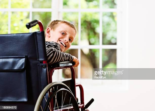 Glücklich blonden Schulkind-Nur Jungen im Rollstuhl scheint sich erholen
