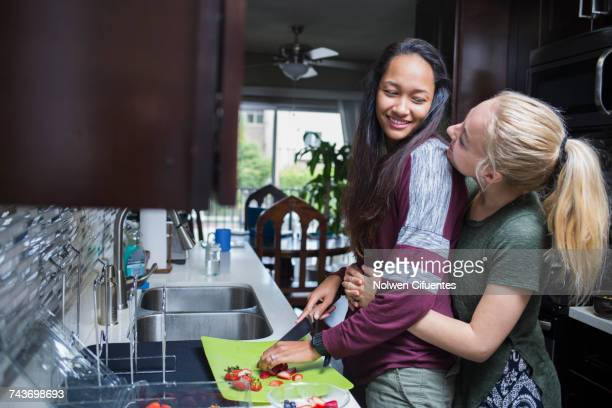Happy blond woman embracing girlfriend cutting strawberries in kitchen at home