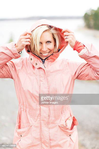 Happy blond woman in raincoat