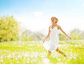 Happy blonde female running across the field.