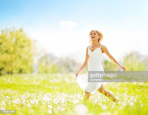 Glückliche blonde Frau läuft über das Feld ein.