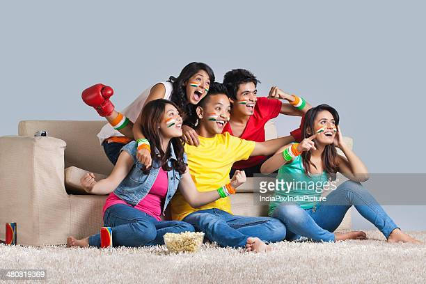 Happy boxing fans cheering together in living room