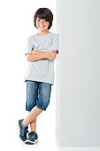 Smiling little boy posing against grey wall isolated on white background. Happy cute child standing against white background. Young boy leaning against a grey sign and looking at camera with arms cros