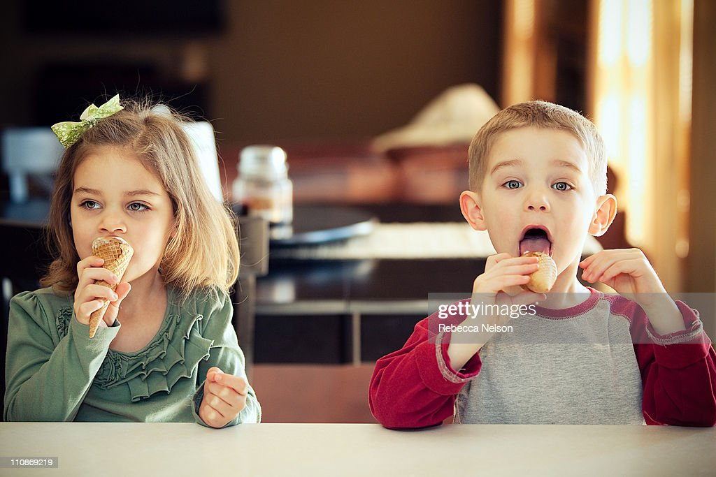 Happy boy and girl eating ice cream cones : Stock Photo