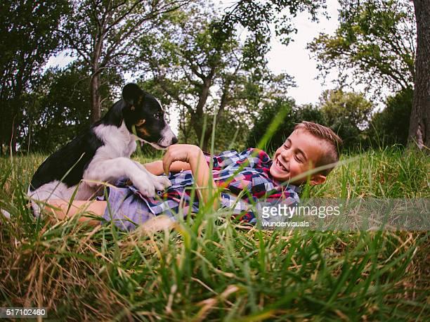 Glücklicher Junge und sein Hund-Hund es sich um im Gras