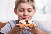 Happy boy eating delicious sandwich with banana and chocolate cream