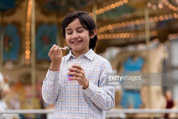 Happy boy eating ice cream at a fun fair