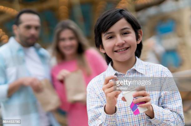 Happy boy eating ice cream at a traveling carnival
