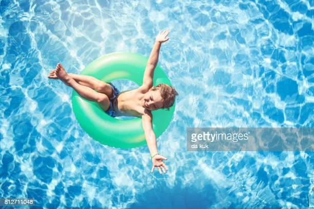 プールで泳ぐリング上に浮かんで幸せな少年
