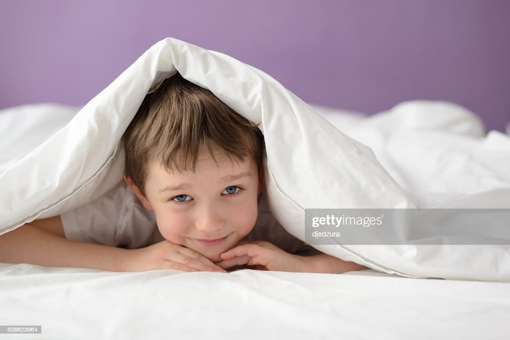 Happy boy hiding in bed under a white blanket : Stock Photo