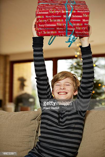 Happy boy holding up present in stretched arms
